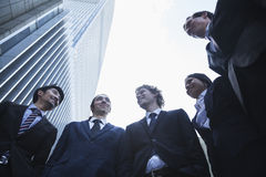 站立五个的商人户外谈话和微笑,北京,低角度视图 库存图片