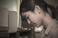 站立介于中间的书架的重音亚洲studentwoman 库存图片