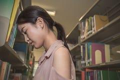 站立介于中间的书架的重音亚洲studentwoman 库存照片