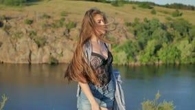 站立以一个大湖为背景的愉快的微笑的女孩 股票录像