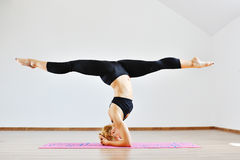 站立体育的衣物的年轻亭亭玉立的体操运动员妇女颠倒 免版税库存图片
