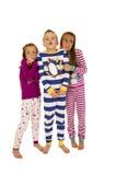 站立佩带的圣诞节睡衣的三个孩子吓唬了exp 免版税图库摄影