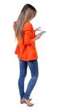 站立使用一个流动响度单位的年轻美丽的妇女后面看法  库存图片