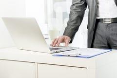 站立使用膝上型计算机的商人 免版税库存图片