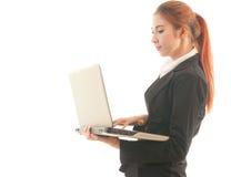 站立使用膝上型计算机的女商人 免版税库存图片