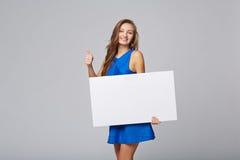 站立全长美丽的妇女后边,举行白色bl 免版税图库摄影
