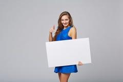 站立全长美丽的妇女后边,举行白色bl 免版税库存图片