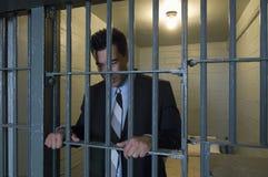 站立关在监牢里的商人 免版税库存照片