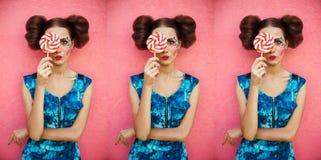 站立反对与许多的桃红色背景甜桃红色圆的棒棒糖掩藏的一半面孔的美丽的女孩 时尚射击画象 免版税图库摄影