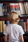 站立反对书架的男小学生在图书馆里 免版税库存照片