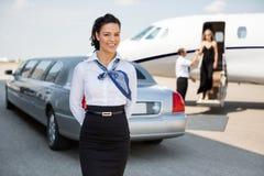 站立反对大型高级轿车的可爱的空中小姐 免版税库存图片