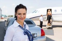 站立反对大型高级轿车的美丽的空中小姐 图库摄影