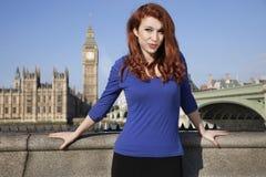 站立反对大本钟钟楼,伦敦,英国的美丽的少妇画象  图库摄影