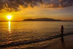 站立反对太阳的一名孤立妇女在芽庄市海滩 库存照片