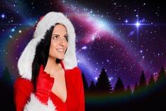 站立反对数位引起的背景的圣诞老人服装的愉快的妇女 库存图片