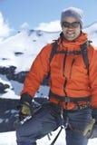 站立反对斯诺伊山的爬山者 免版税库存图片