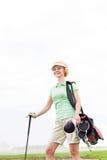 站立反对清楚的天空的低角度观点的微笑的女性高尔夫球运动员 免版税库存照片