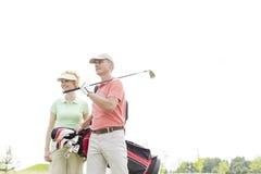 站立反对清楚的天空的低角度观点的微笑的高尔夫球运动员 免版税库存图片