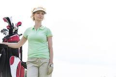 站立反对清楚的天空的低角度观点的确信的女性高尔夫球运动员 免版税库存图片