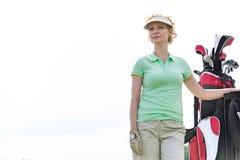 站立反对清楚的天空的低角度观点的确信的女性高尔夫球运动员 免版税图库摄影