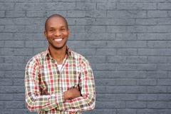 站立反对灰色背景的微笑的非裔美国人的人 免版税库存照片