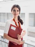 站立反对白色办公室背景的美丽的微笑的女实业家 女商人画象有一个文件夹的在她的手上 库存图片