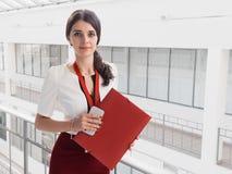 站立反对白色办公室背景的美丽的微笑的女实业家 女商人画象有一个文件夹的在她的手上 免版税库存图片