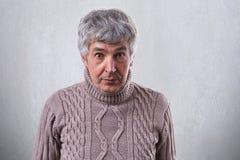 站立反对白色墙壁佩带的毛线衣的资深英俊的人一张水平的画象看充满惊讶入照相机 pe 免版税库存照片