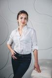 站立反对白色的年轻美丽的妇女 免版税图库摄影