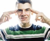 站立反对白色背景的一个聪明的严肃的年轻人的画象 姿态的情感概念 免版税库存照片