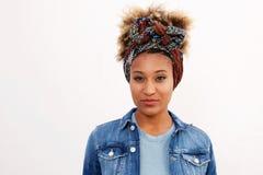 站立反对白色背景的头巾的年轻黑人妇女 免版税库存图片