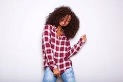 站立反对白色背景的方格的衬衣的时髦的年轻非洲妇女 库存照片