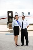 站立反对私人喷气式飞机的空中小姐和飞行员 库存照片