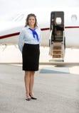 站立反对私人喷气式飞机的美丽的空中小姐 库存照片