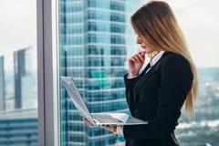 站立反对窗口的体贴的女性CEO在她的私人办公室在拿着膝上型计算机读书的现代商业中心 库存图片