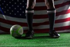 站立反对美国国旗的橄榄球球员的低部分 库存照片