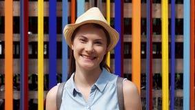 站立反对色的墙壁背景的微笑的妇女 无忧无虑的旅游享用的假期户外 影视素材