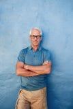 站立反对蓝色背景的确信的成熟人 免版税库存图片