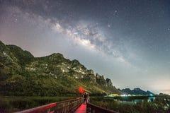 站立反对银河和山,泰国的一个人 免版税库存照片