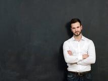 站立反对黑板的一个严肃的年轻人的画象 库存图片