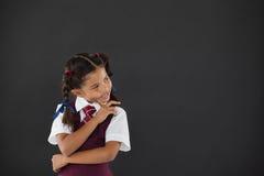 站立反对黑板的女小学生在教室 免版税库存照片