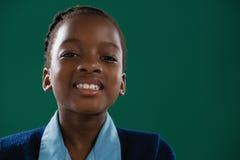站立反对绿色背景的微笑的女小学生 免版税库存图片