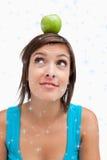 站立可爱的少妇的综合图象挺直用在她的头的一个绿色苹果 免版税库存图片