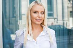 站立可爱的年轻成功的微笑的女商人室外 免版税库存图片