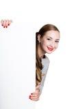 站立后面和倾斜在一张白色空白的广告牌或招贴的微笑的愉快的少妇,表达不同 免版税库存图片