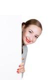 站立后面和倾斜在一张白色空白的广告牌或招贴的微笑的愉快的少妇,表达不同 图库摄影