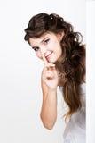 站立后面和倾斜在一张白色空白的广告牌或招贴的微笑的愉快的少妇,表达不同 免版税库存照片