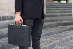 站立和举行公文包手中运作的机智的商人 库存图片