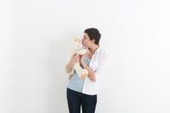 站立和亲吻她的白色和可爱的长毛绒猫的妇女 免版税库存图片