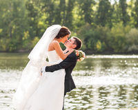 站立和亲吻在湖附近的婚礼夫妇 库存照片